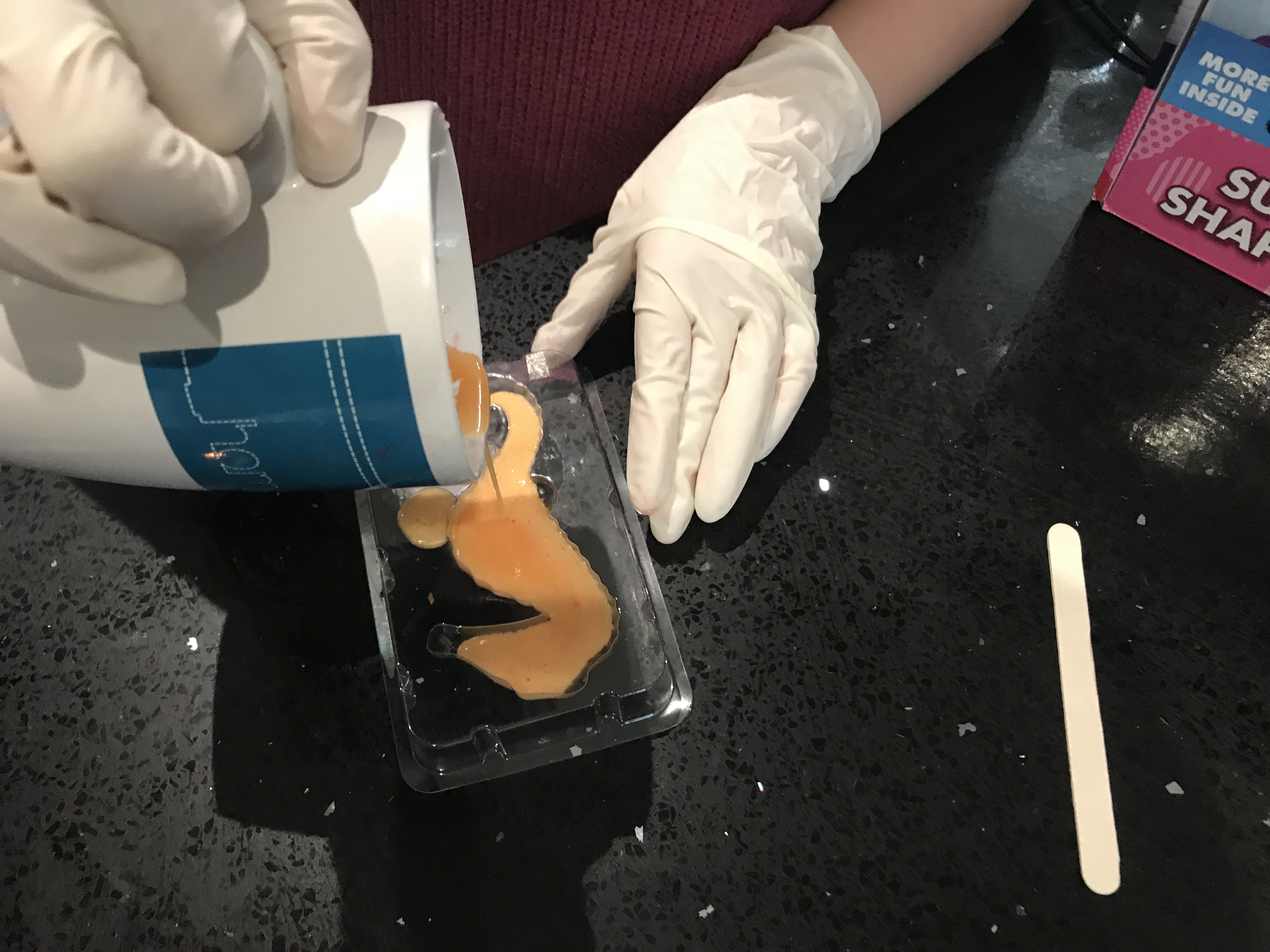 pouring the orange soap into a seahorse mould